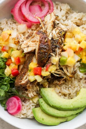 Bowl of crock pot jerk chicken with rice and avocado.