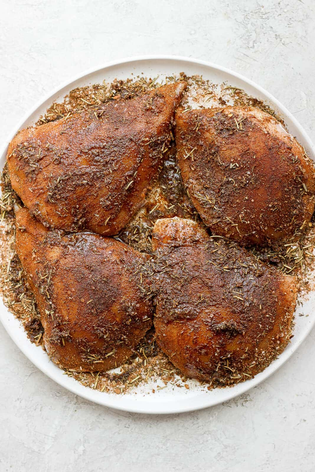 Chicken covered in jerk seasoning on a plate.