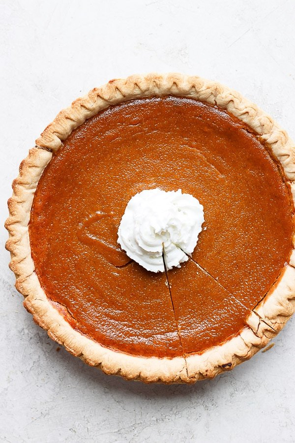 Dairy free pumpkin pie with whipped coconut cream in the center.