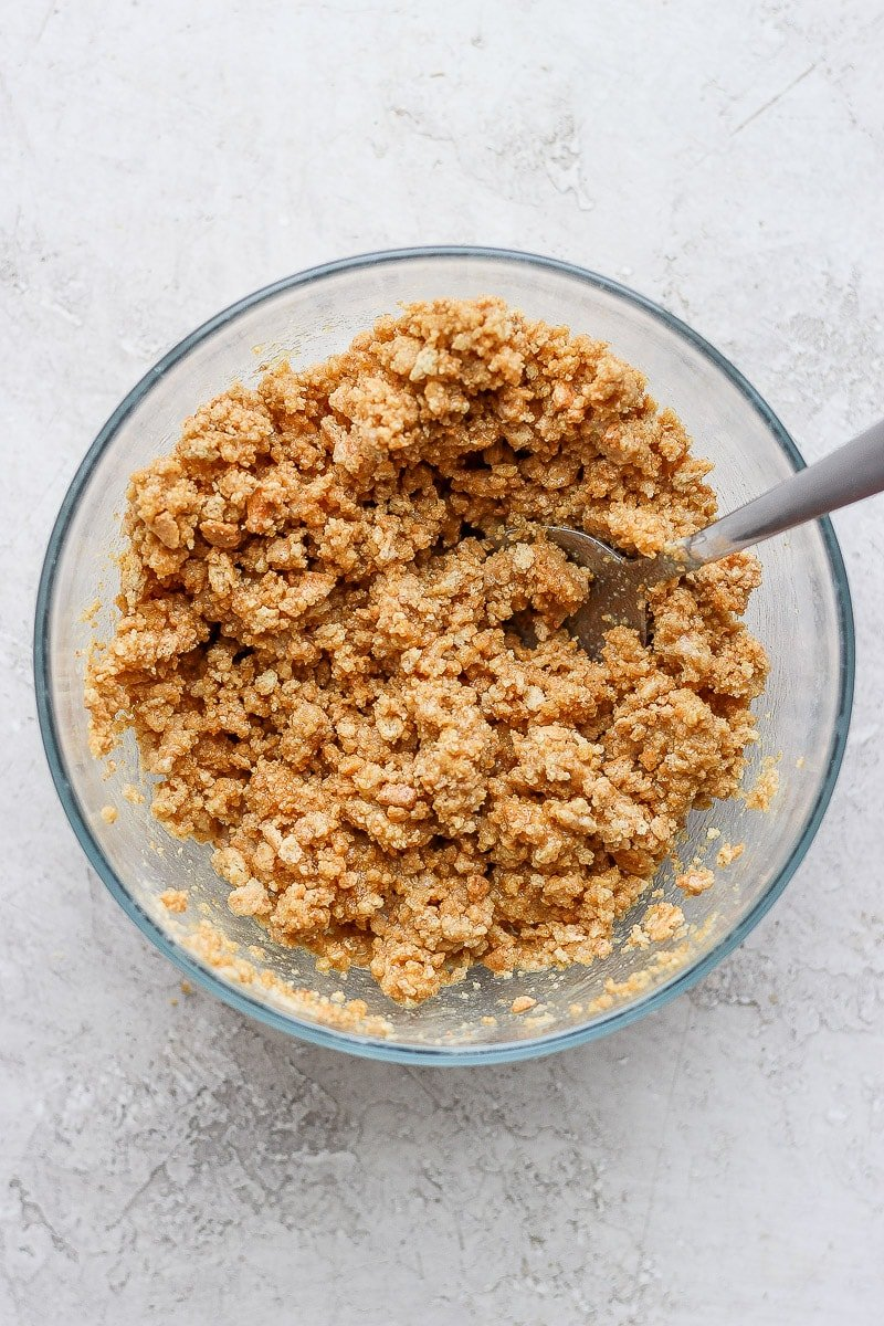 Bowl of crushed graham cracker and melted vegan butter.