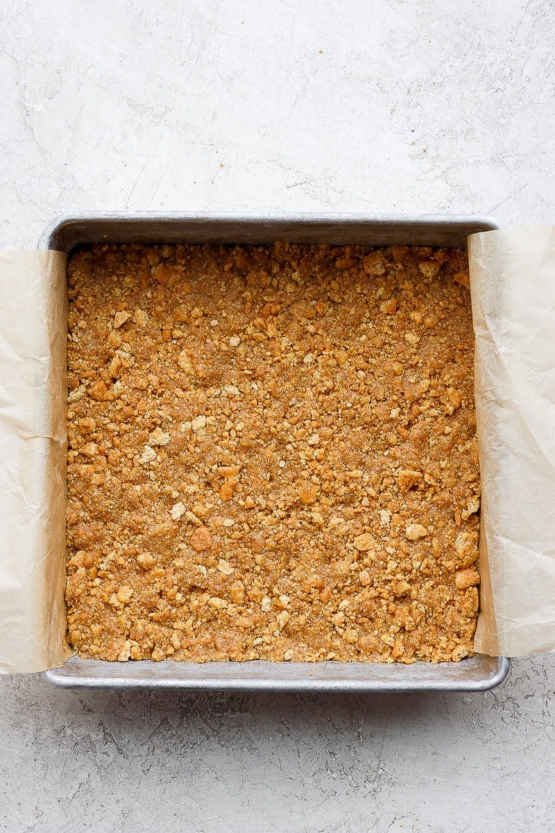 9x9 pan lined with parchment and a graham cracker crust pressed down on the bottom.