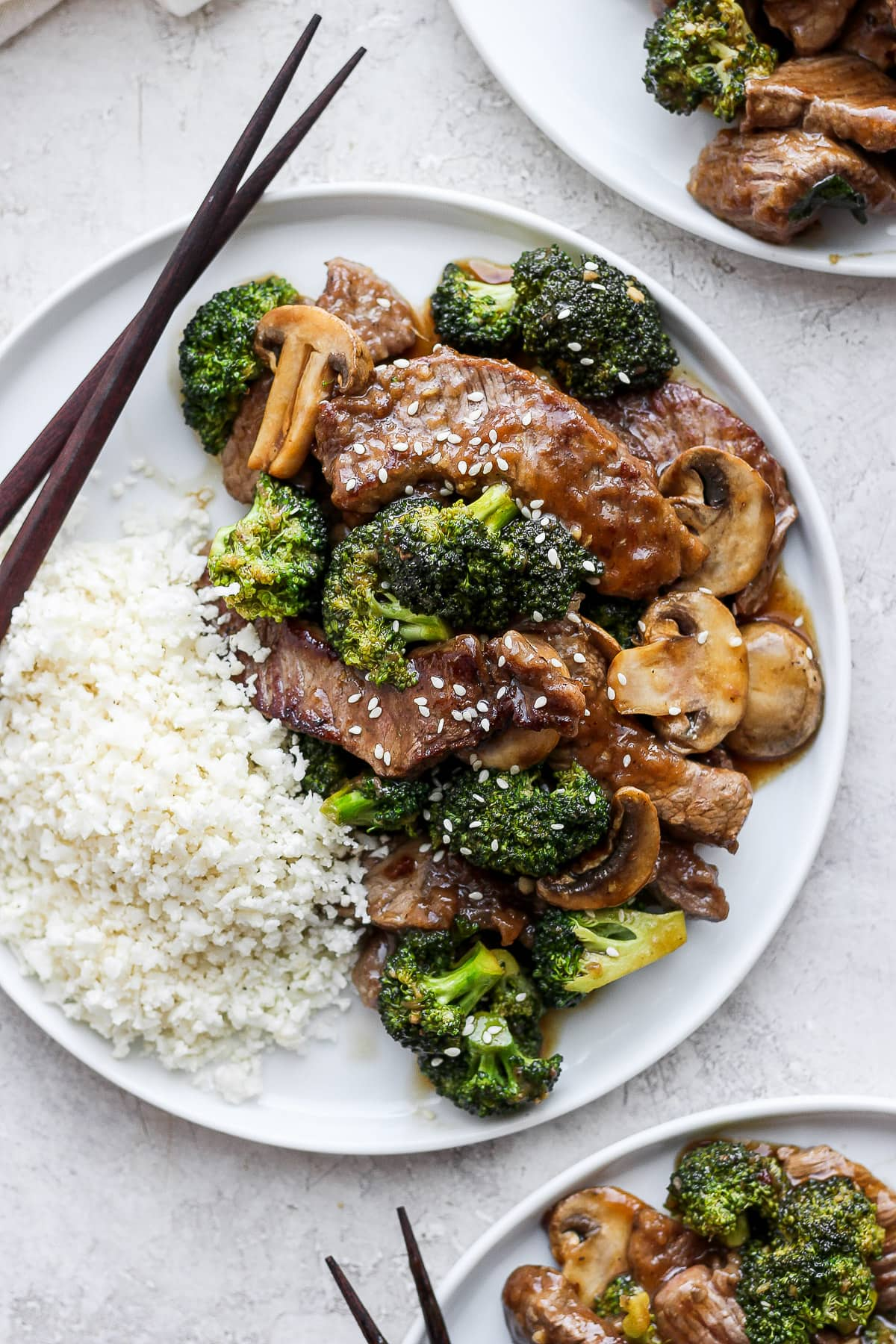 Plate of healthy beef and broccoli with cauliflower rice and chopsticks.