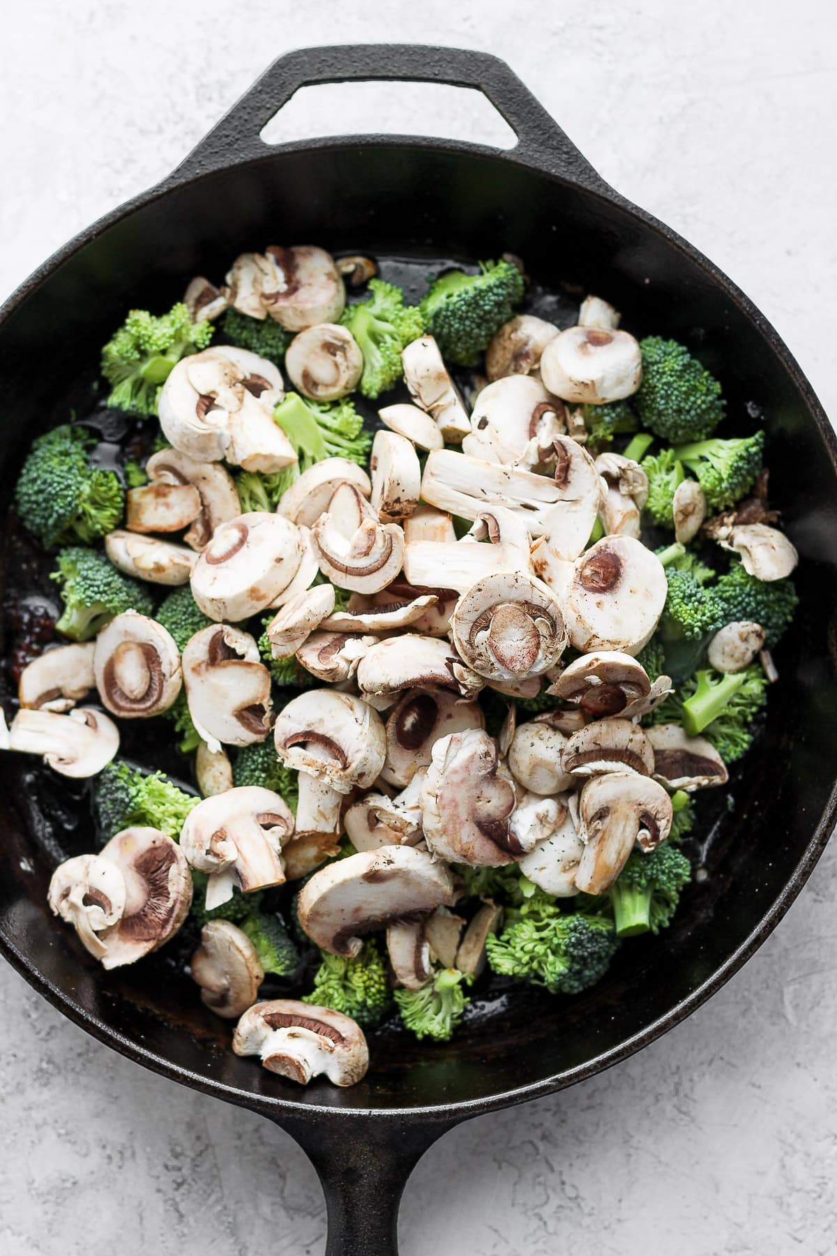 Cast iron skillet with broccoli and mushrooms.