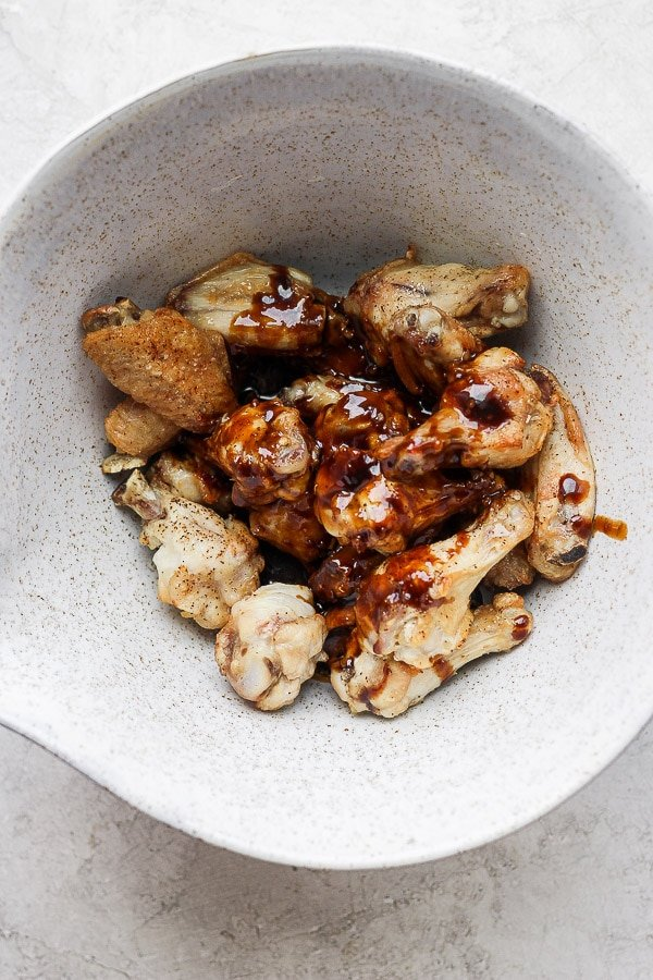 Baked wings in a large bowl with ginger sesame sauce poured on top.