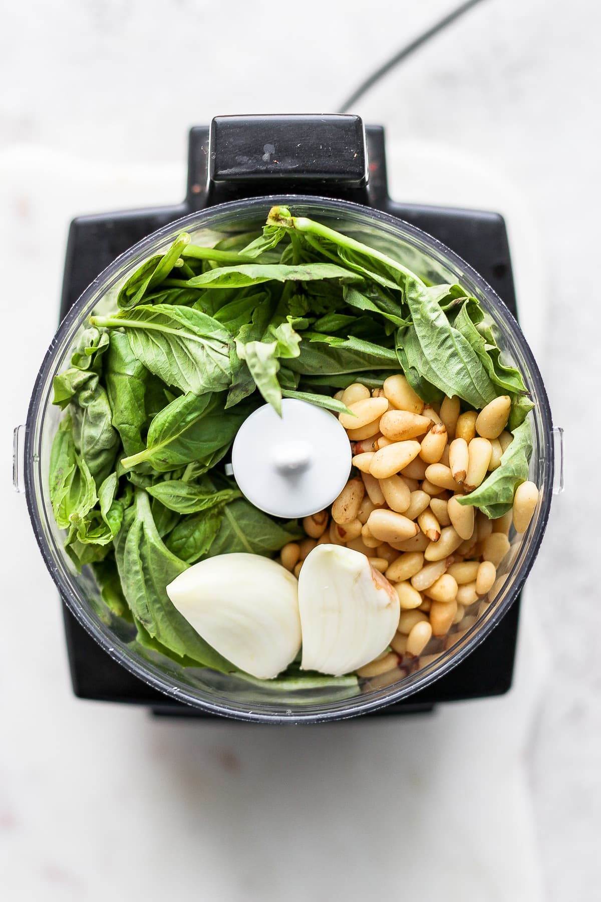 A top shot of a food processor filled with fresh basil, pine nuts and garlic cloves.