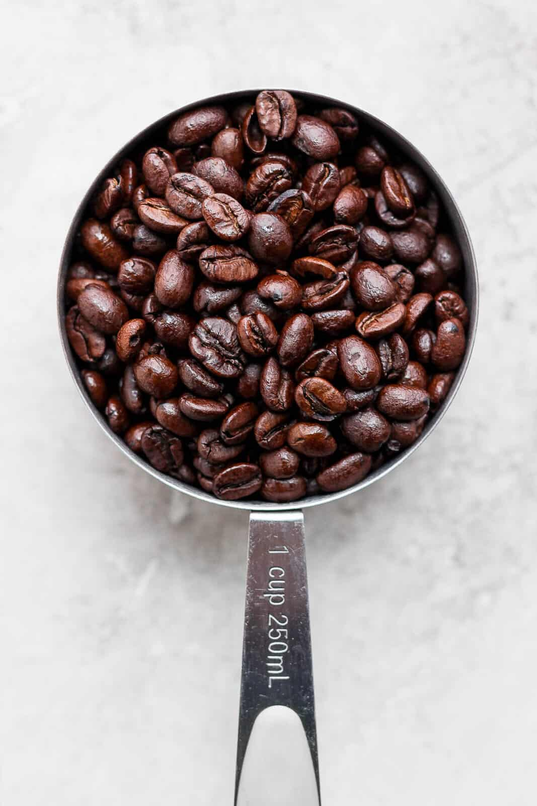A measuring cup filled with whole coffee beans.