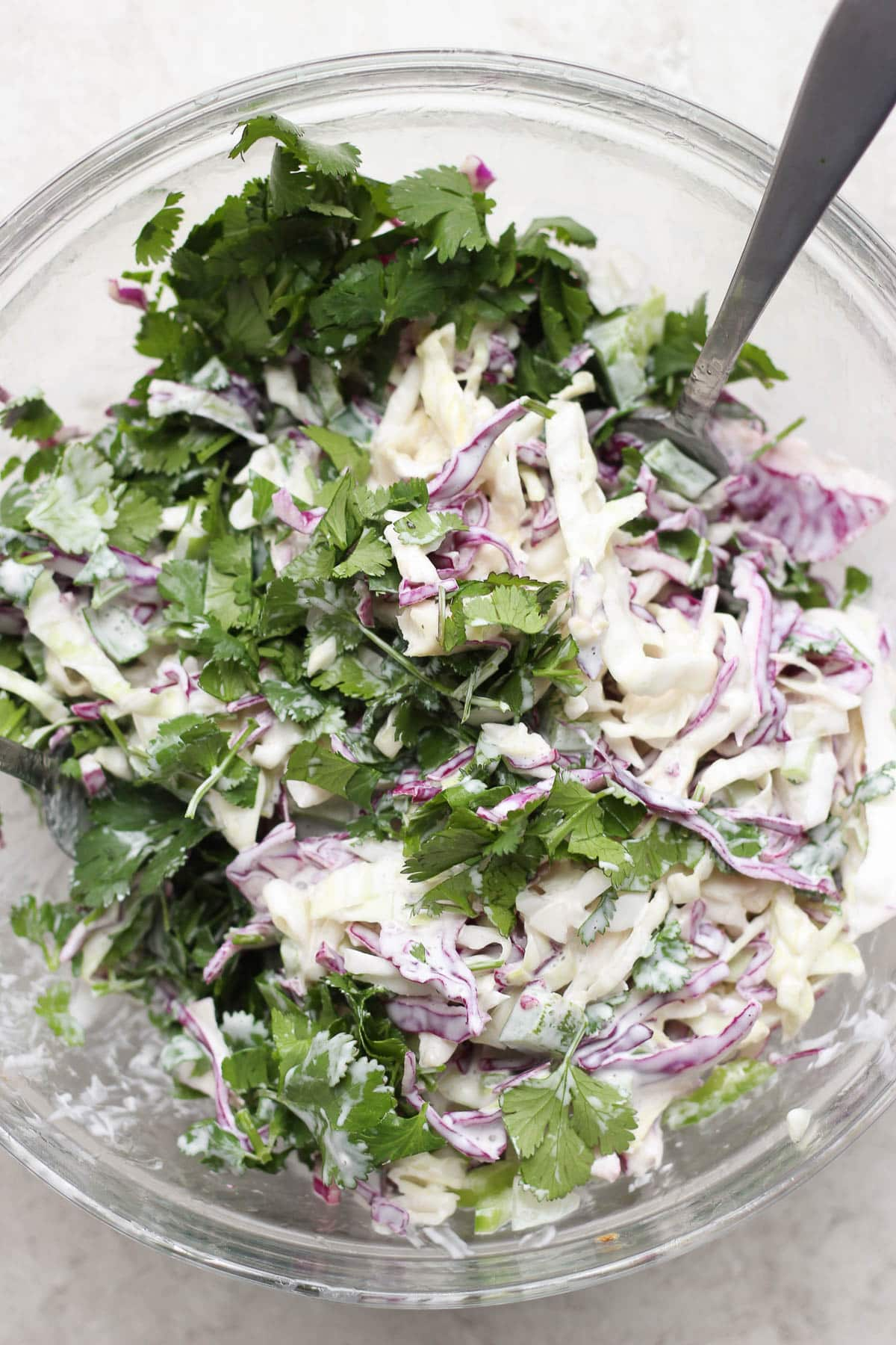 Glass bowl full of spicy purple cabbage coleslaw.