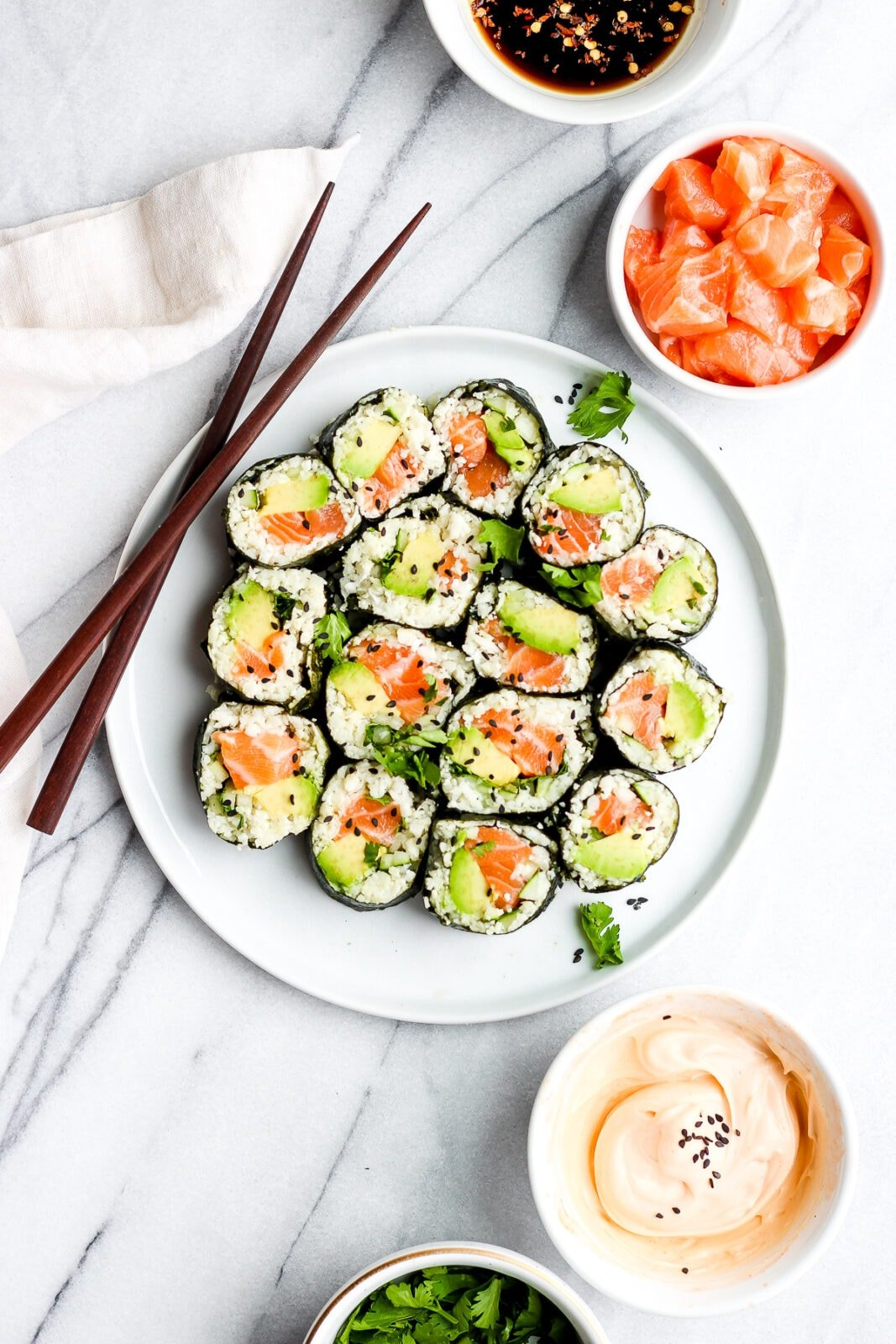 Spicy Salmon and Avocado Cauliflower Rice Sushi Roll on a plate with chopsticks.