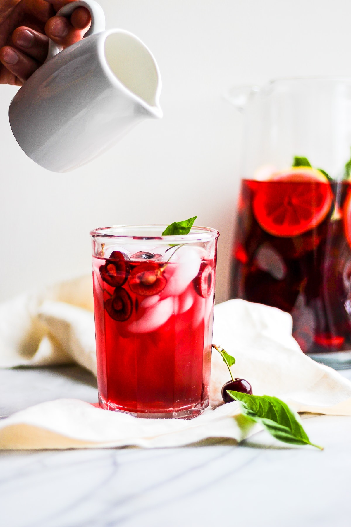 Glass of hibiscus tea on a marble board with someone pouring dairy-free creamer into it.  There is a pitcher of more tea in the background.