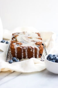 Paleo Blueberry Muffin Bread + Vanilla Glaze - a delicious paleo breakfast that your whole family will love! #paleo #bananabread #blueberrymuffin