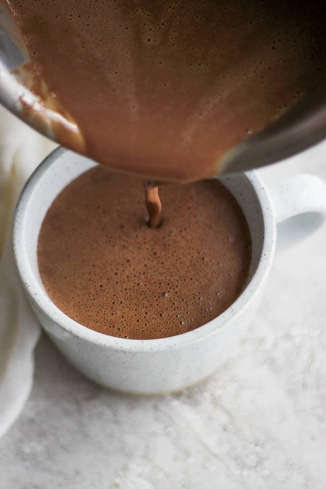 Top shot of someone pouring dairy-free hot chocolate into mug.