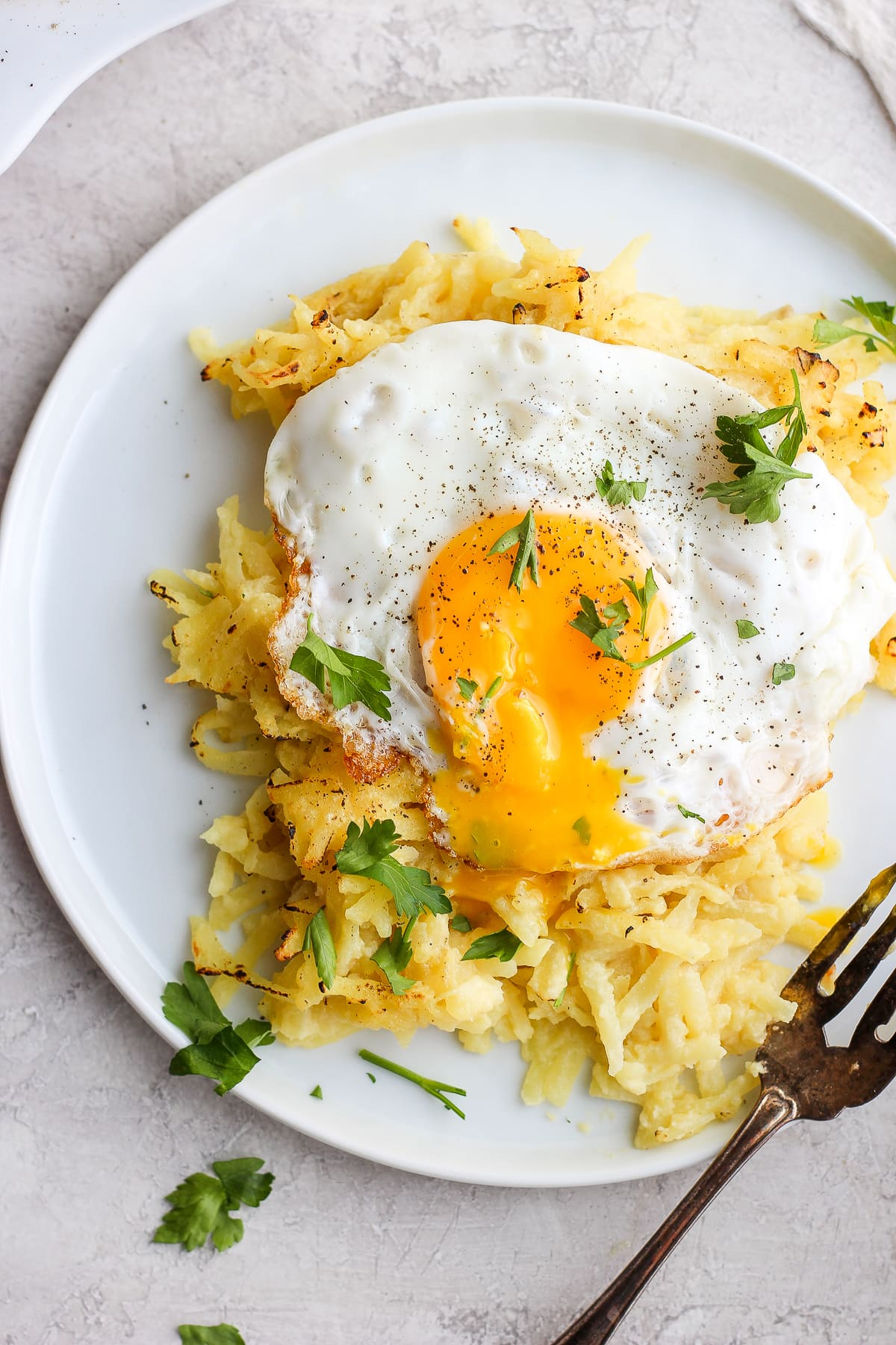 Dairy Free Cheesy Hashbrown Bake on a plate with an egg on top.