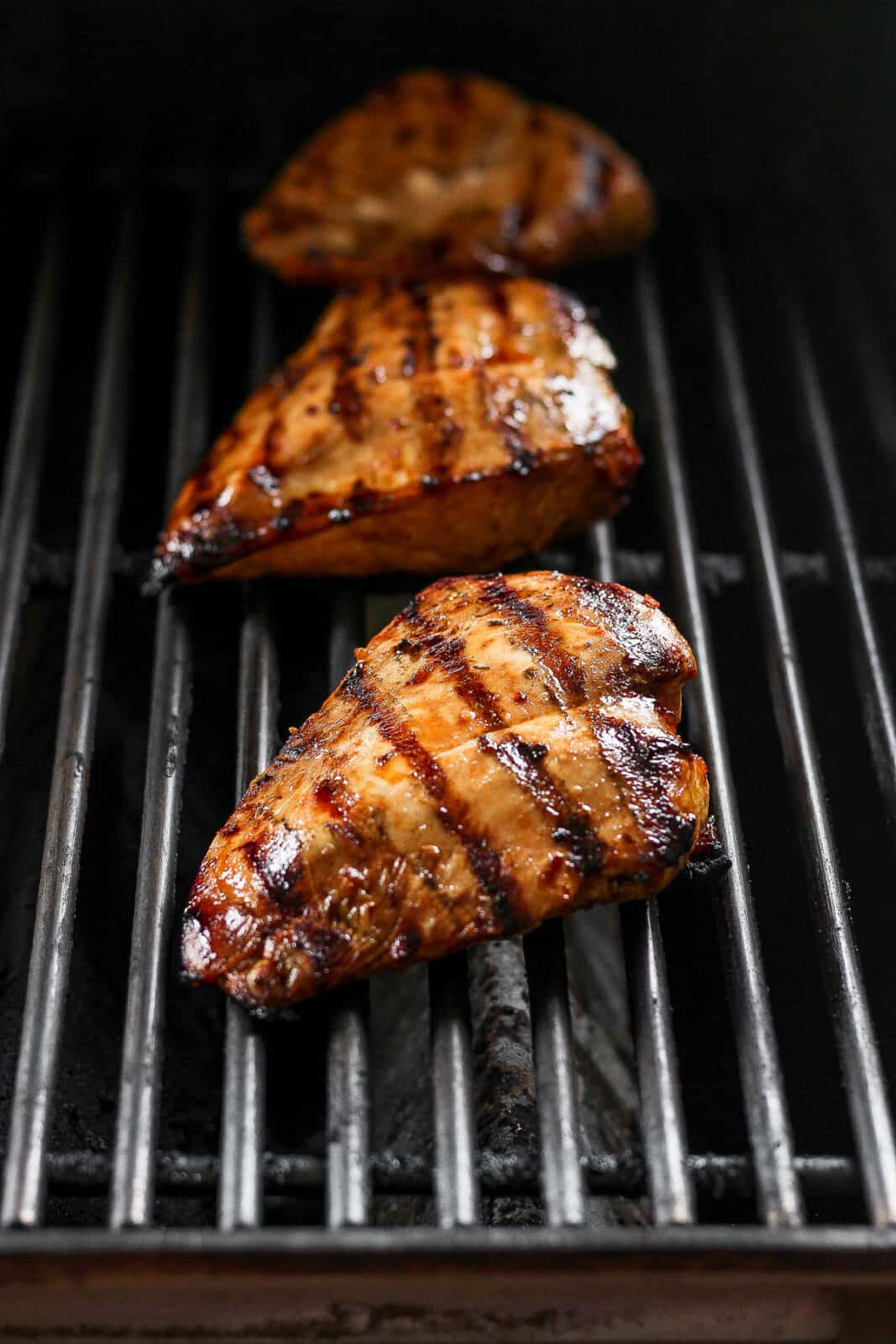 Three chicken breasts on the grill.