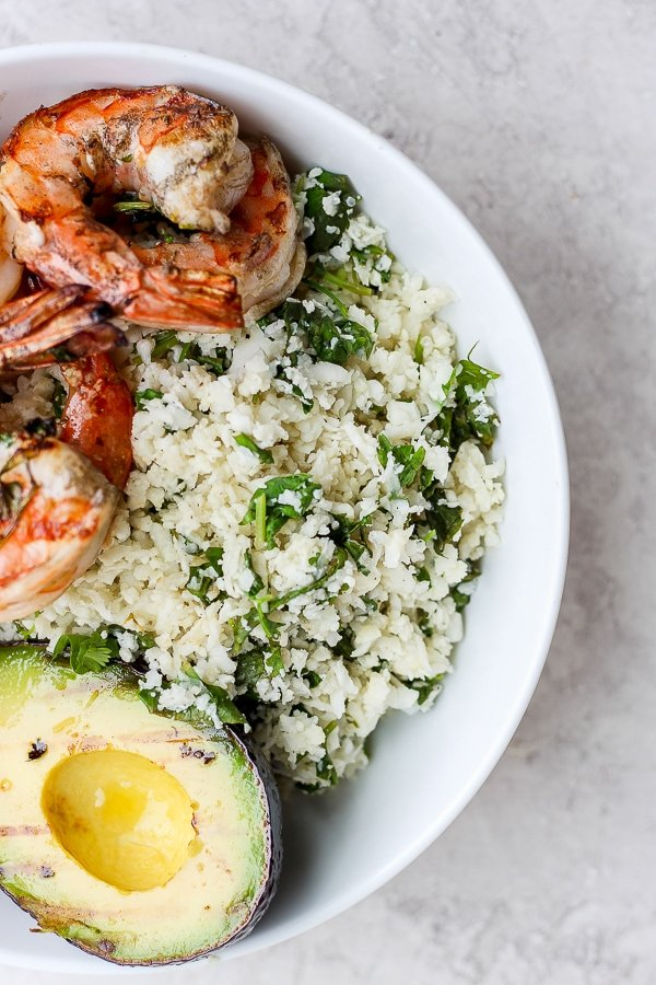Cilantro Lime Cauliflower Rice in a bowl with avocado and shrimp.
