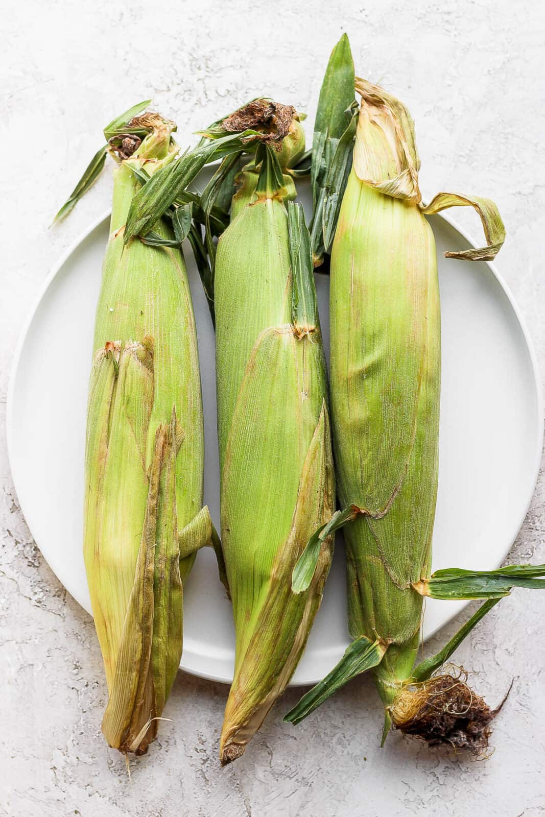 Three pieces of corn with husks on on a plate.