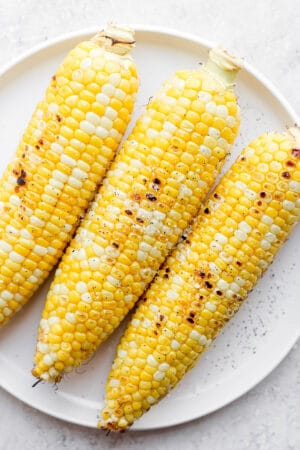A plate of three grilled pieces of sweet corn.