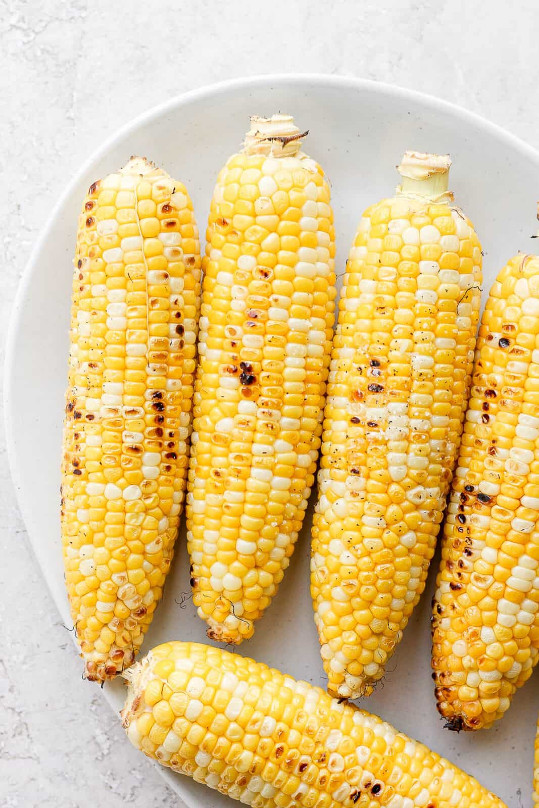 A platter of five pieces of grilled sweet corn.