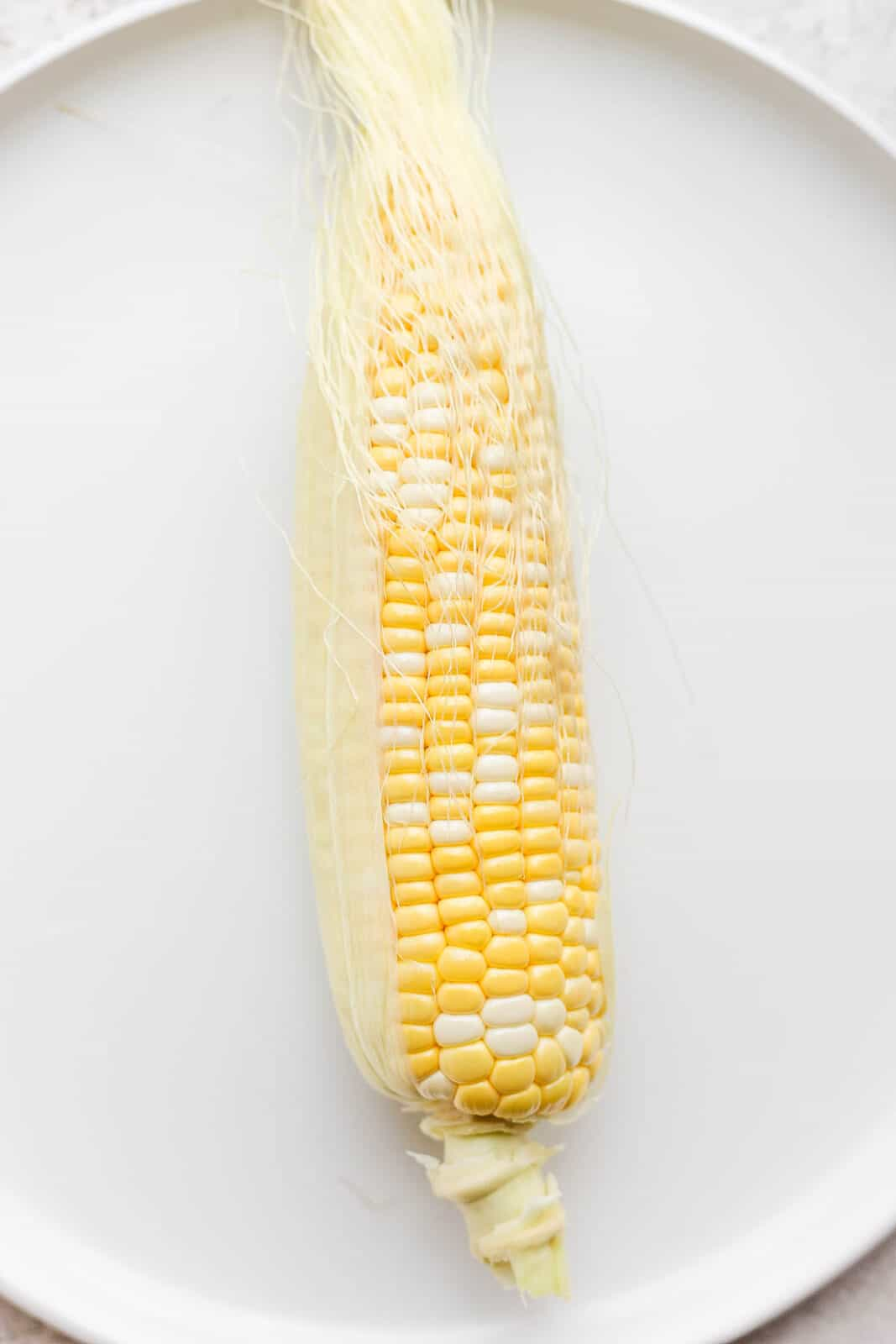 One piece of sweet corn on a plate with husk removed.