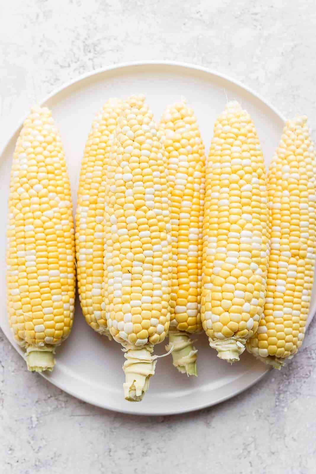 Six pieces of sweet corn on a plate.