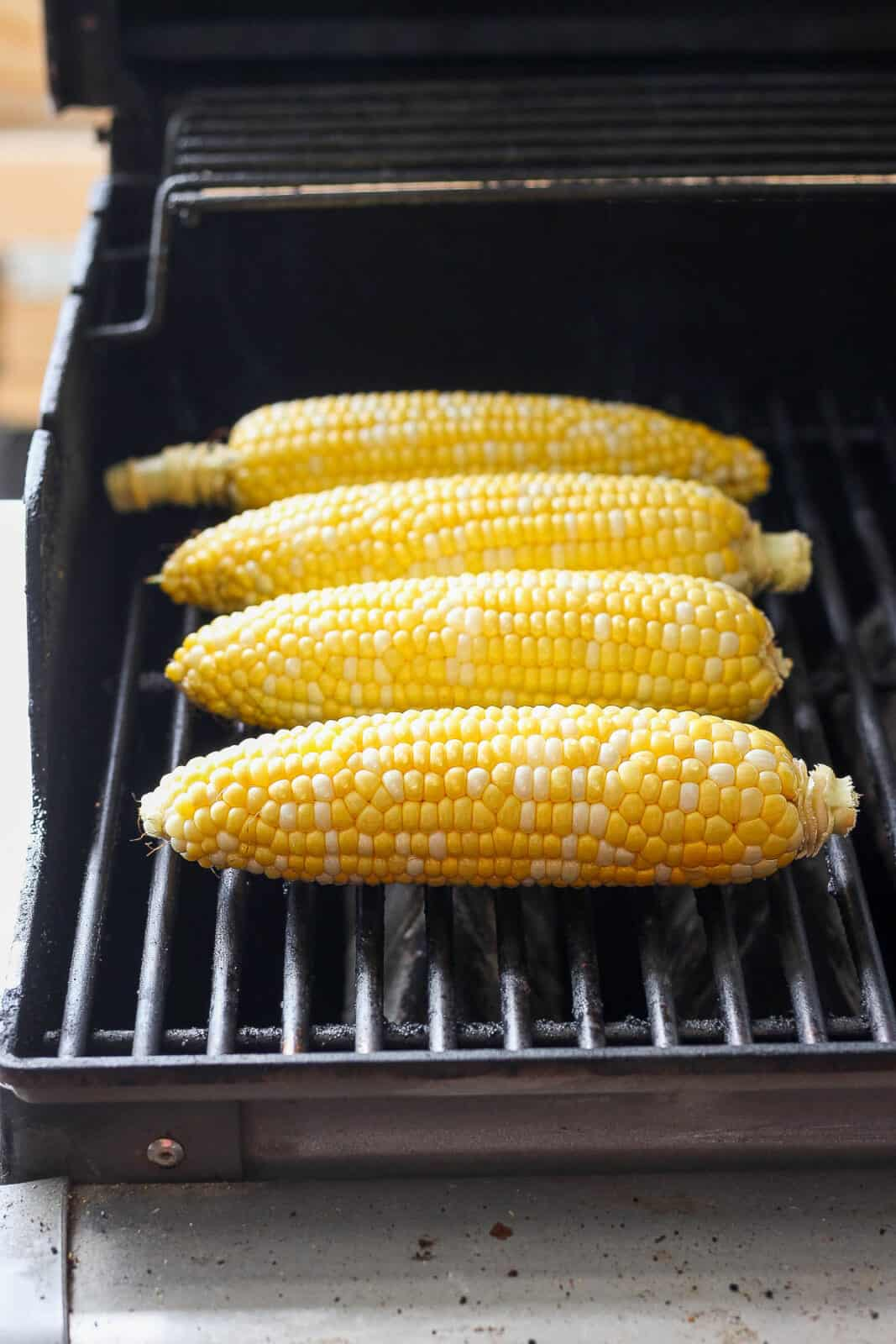 Four pieces of sweet corn on the grill.