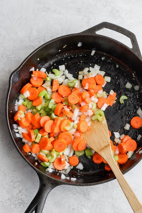 Carrots, onion and celery being sautéed in a cast iron skillet.