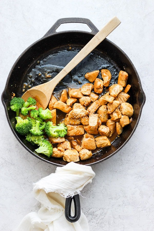 Healthy Orange Chicken and broccoli in a large cast iron skillet.