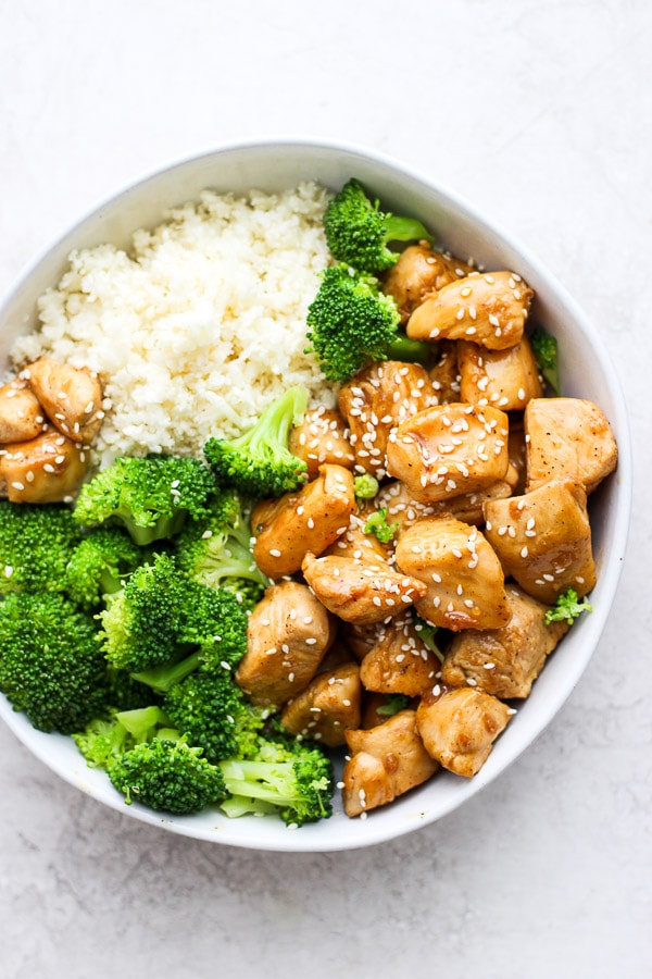 Healthy Orange Chicken in a bowl with broccoli and cauliflower rice.