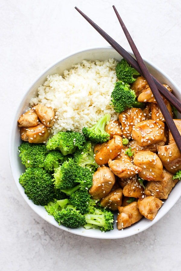 Bowl of Healthy Orange Chicken with broccoli and cauliflower rice.