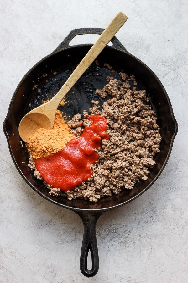 Cast iron skillet with ground beef, taco seasoning and tomato sauce.