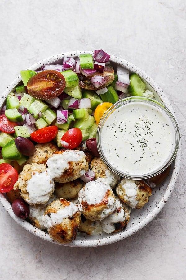 greek chicken meatballs in a bowl with homemade tzatziki sauce.