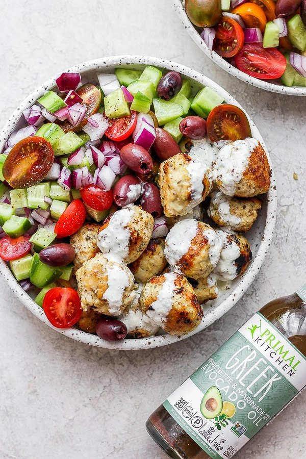 greek chicken meatballs in a bowl with greek salad and homemade tzatziki sauce and a bottle of greek dressing.
