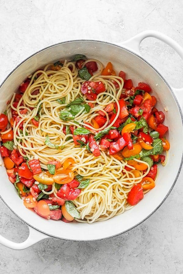 A Dutch oven filled with spaghetti and bruschetta mix.