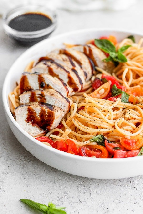 A bowl of bruschetta chicken pasta with tomatoes, fresh basil and a grilled chicken breast drizzled with balsamic glaze.