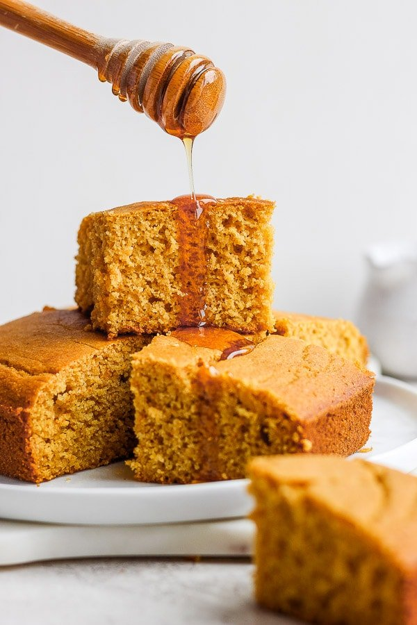 Slices of cornbread on a plate with honey being drizzled over the top.