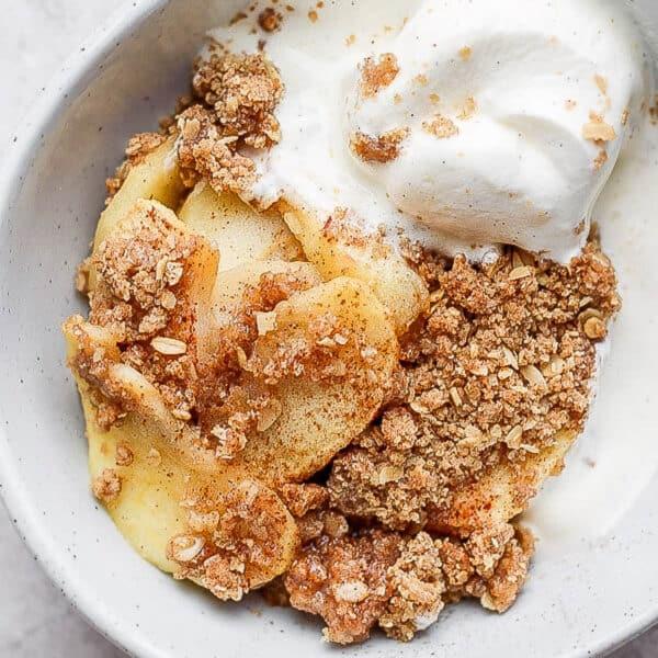 Healthy Apple Crisp Recipe in a bowl with dairy-free vanilla ice cream.