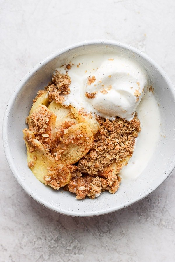 Healthy Apple Crisp in a bowl with dairy free ice cream.
