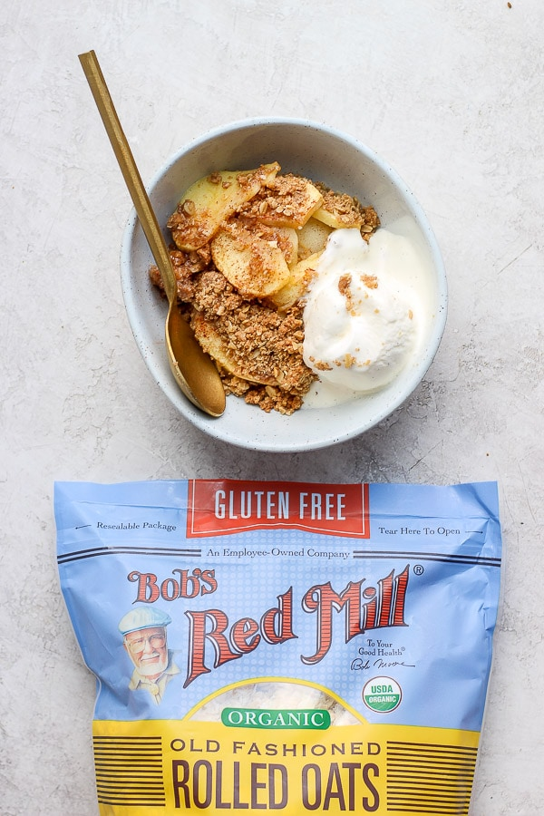 Healthy Apple Crisp in a bowl with a bag of bob's red mill rolled oats underneath.