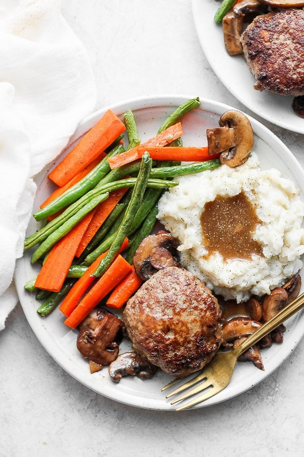Healthy Homemade Salisbury Steak on a plate with mashed potatoes and gravy and roasted veggies.