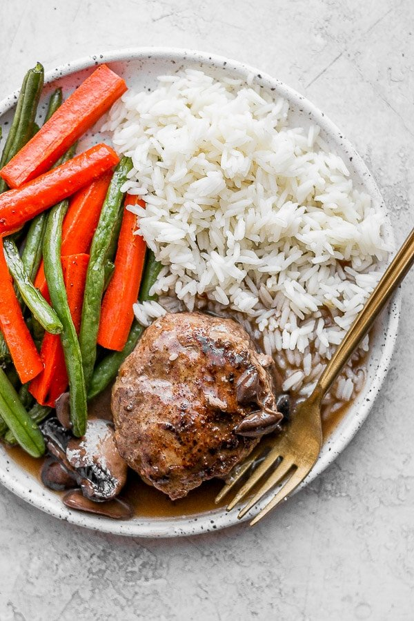 Healthy Homemade Salisbury Steak on a plate with rice and roasted veggies.