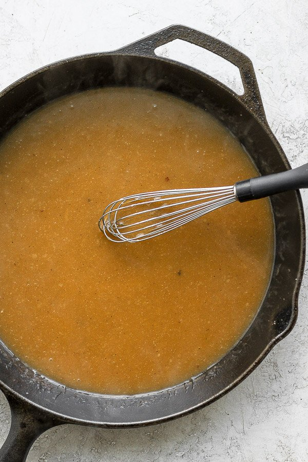 Gravy in cast iron skillet with metal whisk.