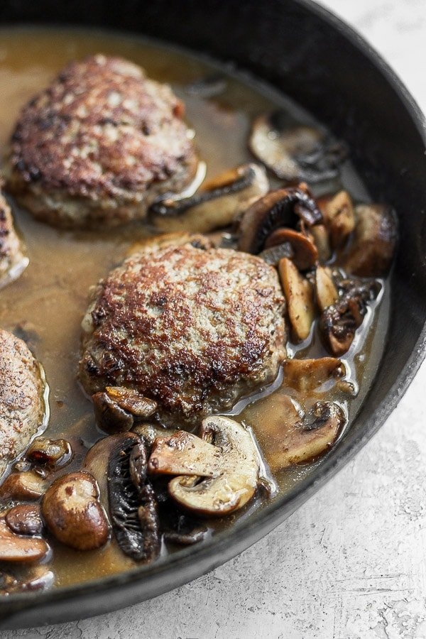 Salisbury steak in cast iron skillet surrounded by gravy and mushrooms.
