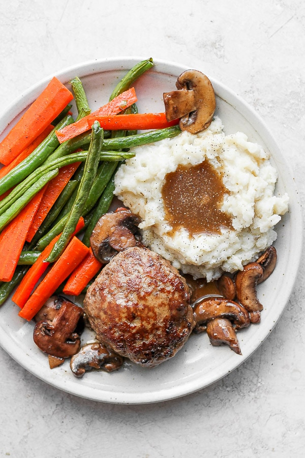 Healthy Homemade Salisbury Steak on a plate with mashed potatoes, gravy and roasted veggies.