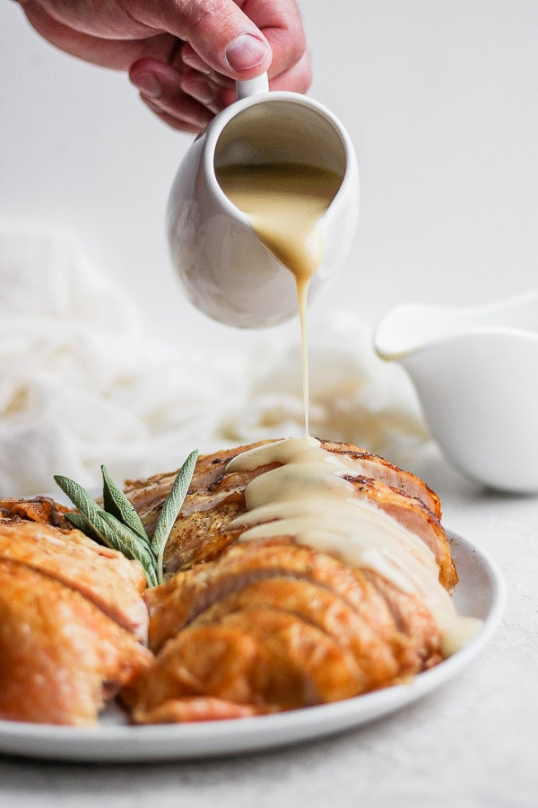 Turkey gravy is being poured on slices of cooked turkey on a plate.
