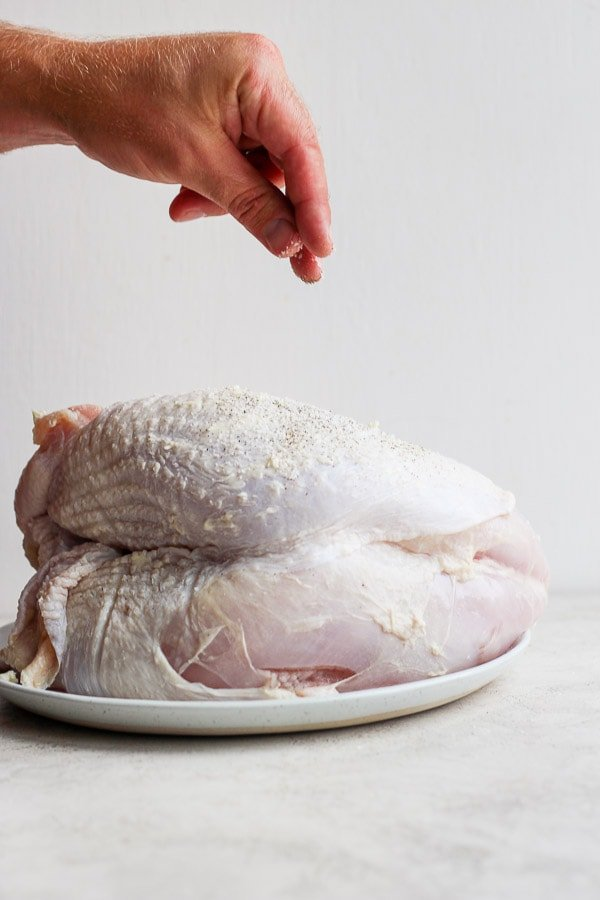 A hand seasoning a raw turkey breast with salt and pepper.