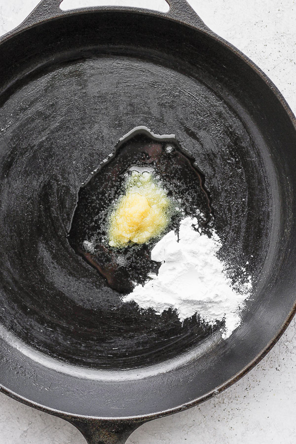 Cast iron skillet with melting ghee and tapioca starch in the middle.