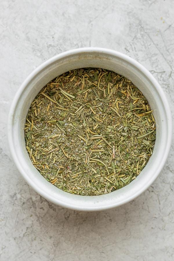 A small white bowl full of all the herbs needed to make gluten free stuffing.