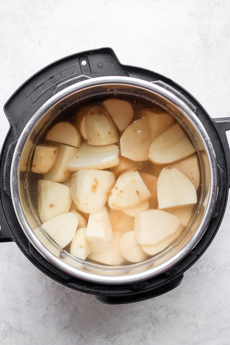 Instant pot with chunks of peeled russet potatoes and water to cover them.