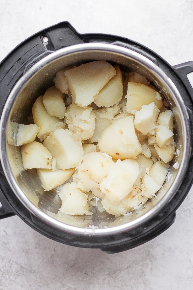 Instant Pot with cooked potatoes that have been drained and returned to the Instant Pot.