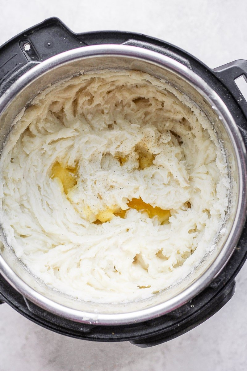An Instant Pot with mashed potatoes and some melted ghee.