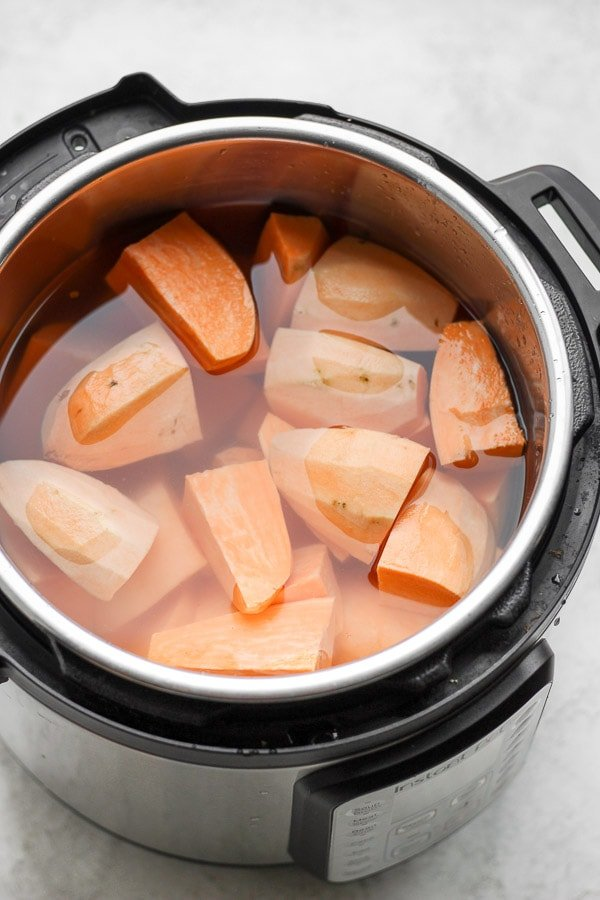 Peeled and cut-up sweet potatoes in an InstantPot with water barely covering them.